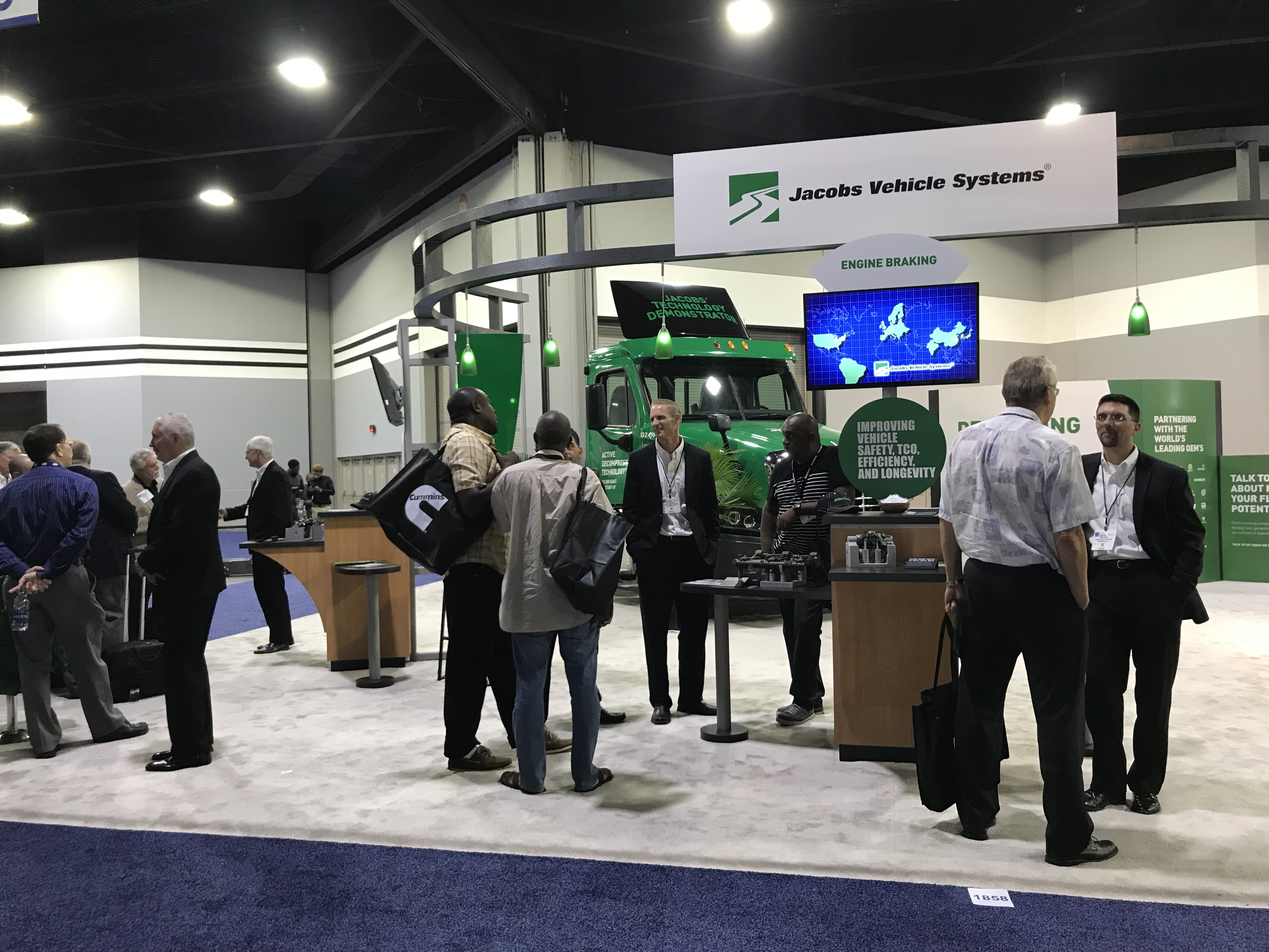 Image of Jacobs Vehicle Systems' 2017 NACV Booth.  Groups of people stand in the booth asking questions.  The booth is white and green.  There is a green semi truck parked in the booth.