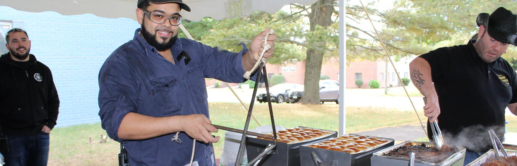 Man with hat, glasses, and beard holding a metal triangle to make noise signifying the start of the meal.  He is standing in front of a buffet of BBQ outside under a tent.  A man in a black shirt and black cowboy hat is serving food.