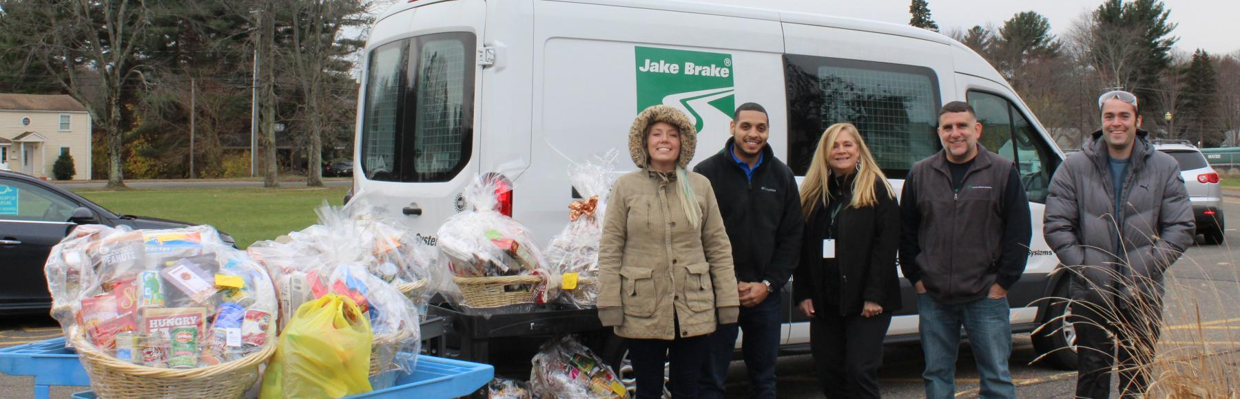 Group of five Jacobs employees wearing winter coats while standing outside in front of a white delivery van with a Jake Brake logo on the side.  There are also rolling carts which are holding gift baskets that contain food and supplies for Thanksgiving.