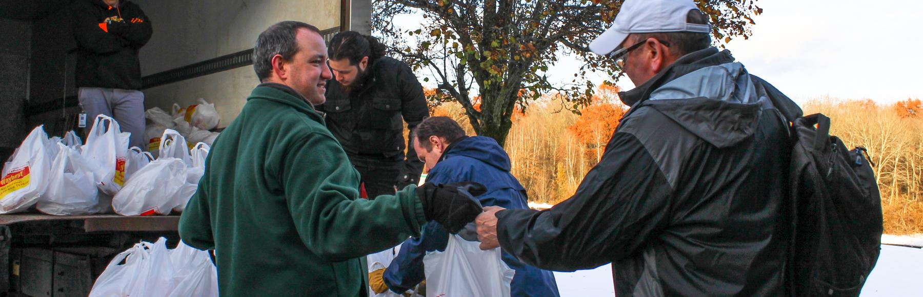 A man in a green jacket and blue jeans hands a sack filled with a turkey to a man with a white baseball cap with a black jacket, blue jeans and a backpack.  Three other men are in the background standing in or beside a small refrigerated box truck which contains more sacks of turkeys which will be handed out.