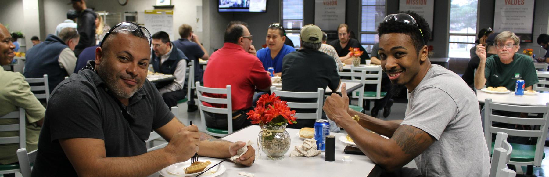 Two men sit at a table in a cafeteria.  They are smiling at the camera while enjoying a Thanksgiving meal.  In the background are more tables with more employees eating meals.