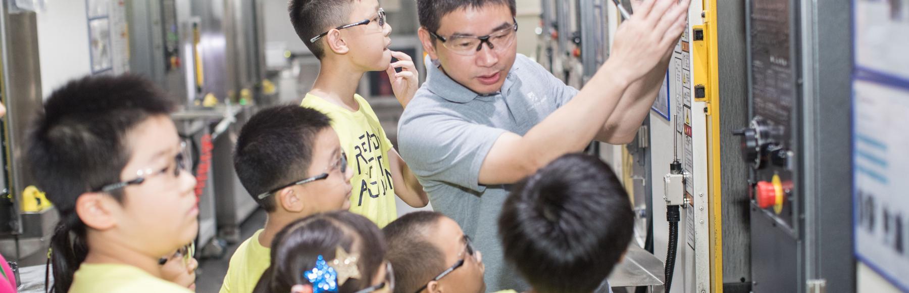 Eine Gruppe von Kindern in gelben Hemden, die vor einer Produktionsanlage stehen. Ein Mann in einem grauen Hemd erklärt ihnen die Funktionsweise der Maschine.