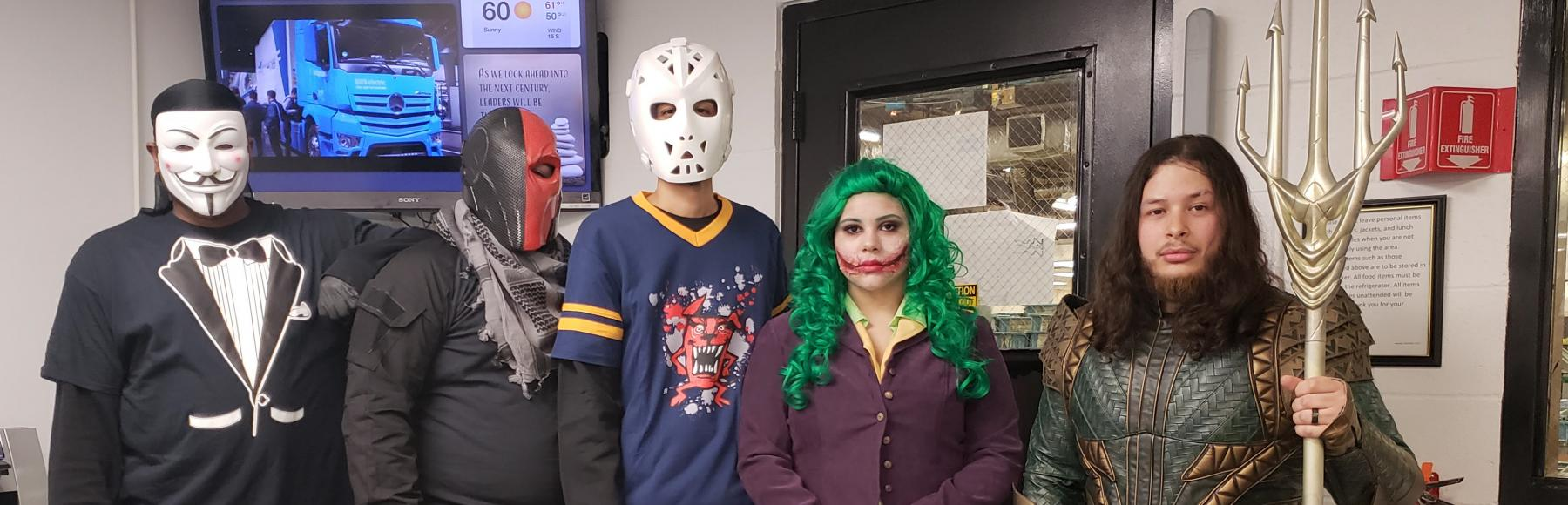 Group of employees dressed up in Halloween costumes.  The group dresses as comic book characters.