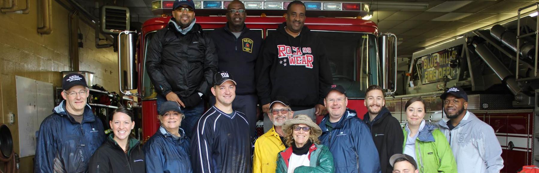 A group of Jacobs employees and Blue Hills Fire Department fire fighters in front of a fire truck after planting flowers.