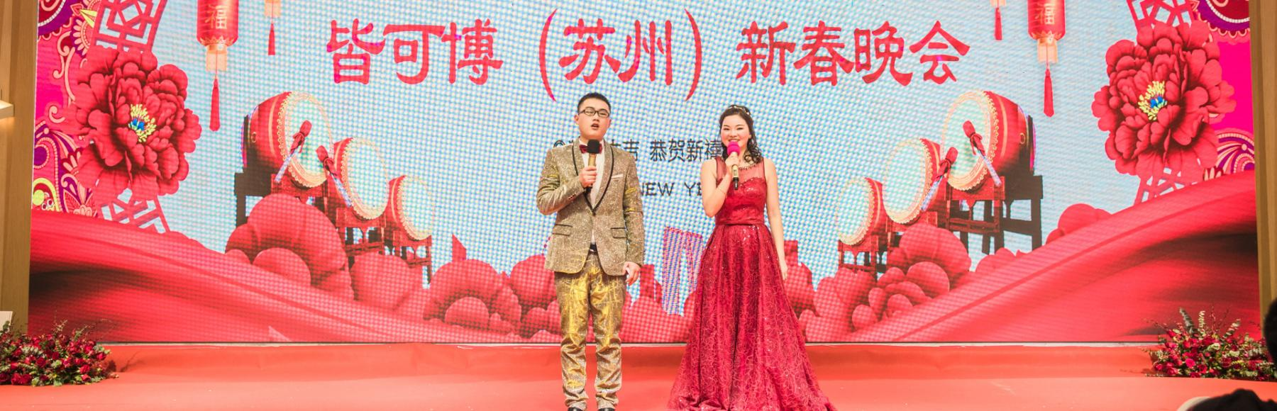 Man dressed in suit and women dressed in a red long gown stand on a stage