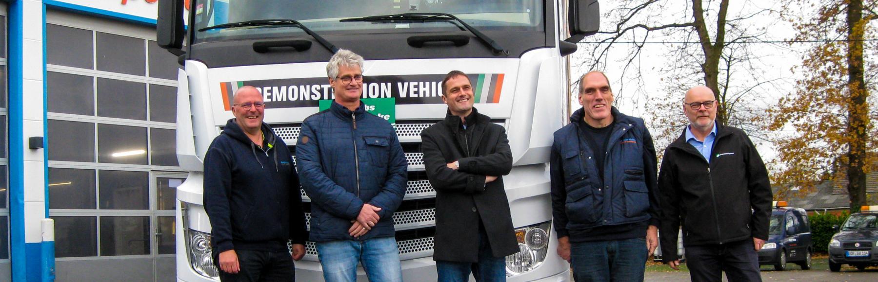 """Fünf Männer stehen nach einem """"Rideand Drive""""-Event vor einem europäischen Demo-Lkw von Jacobs."""