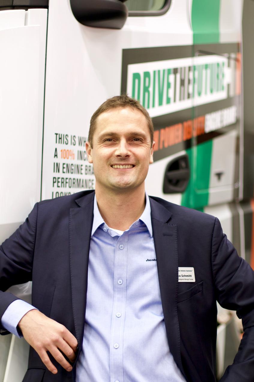 Hilko Schmitt steht vor einem Jacobs Vorführ-Lkw mit hoher Leistungsdichte.